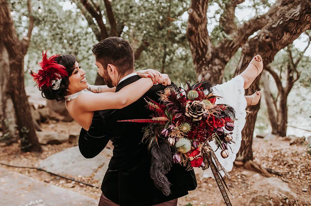 groom carrying bride at vintage circus wedding